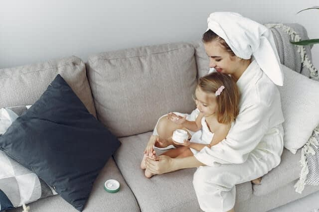 Woman-applying sunscreen with baby